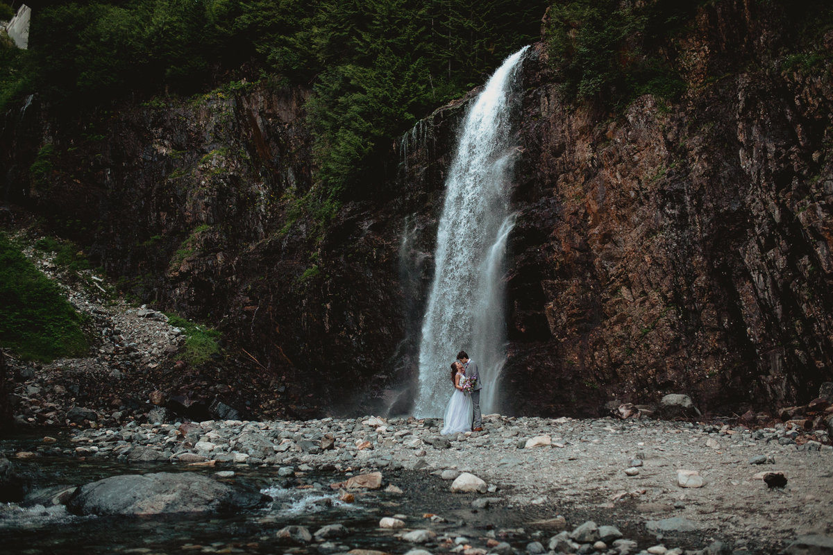Epic elopement wedding in front of a waterfall in the Pacific Northwest during their elopement wedding outside of Seattle Washington