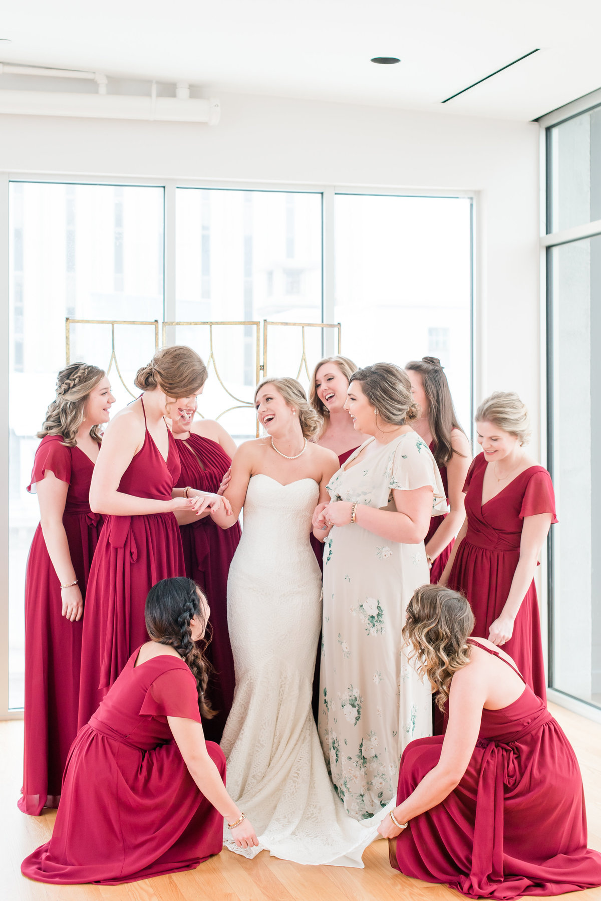 a bride wearing a strapless wedding dress surrounded by her bridesmaids wearing red dresses looking at each other and laughing at the Glassbox at 230 in Raleigh NC