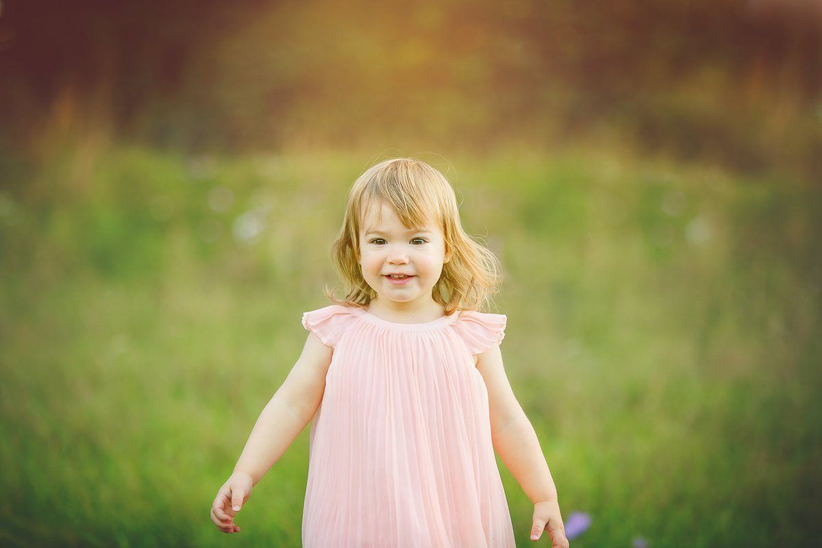 little girl in pink dress meadow field