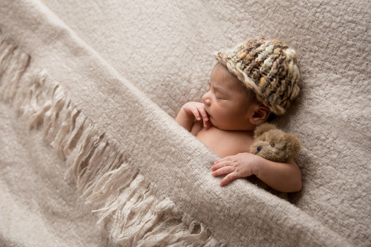 Infant newborn baby boy sleeping pictures with teddy bear and hat, tucked into a blanket in Cornwall NY photo studio by Hudson Valley Photographer