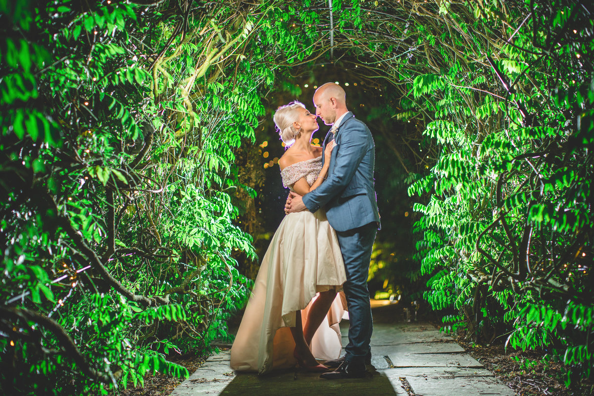 evening wedding photo of bride and groom in an archway of trees