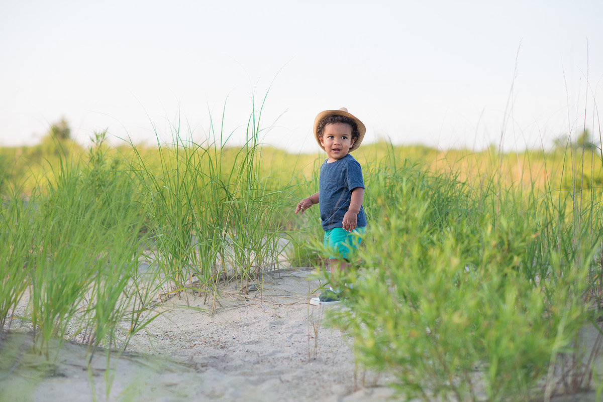 a baby boy runs in the sand dunes at the beach