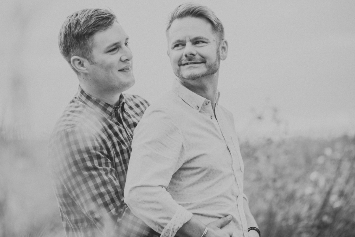 LGBT couple hugging in grass field by Lancashire Wedding Photographer Jono Symonds