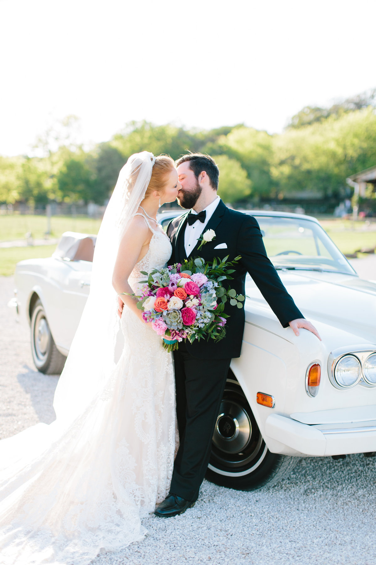 Bride and Groom kissing against their getaway vintage car.