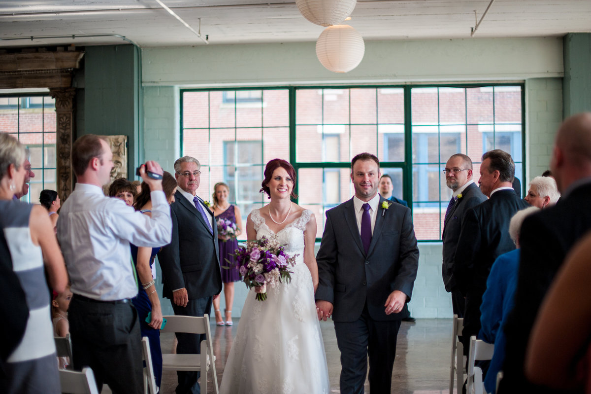 St Louis wedding bride and groom down the aisle City Museum