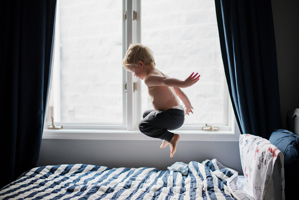 a toddler boy jumps on his bed