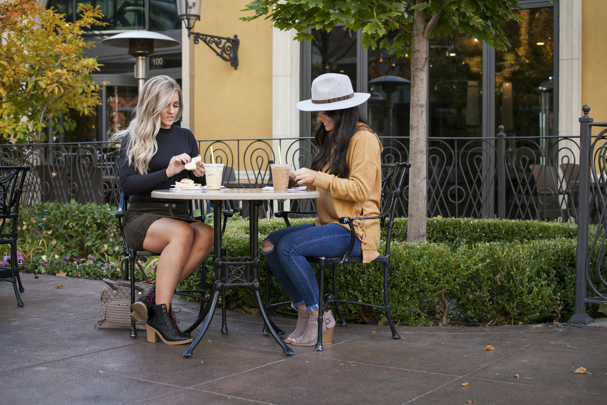 two girls sitting outside eating brunch