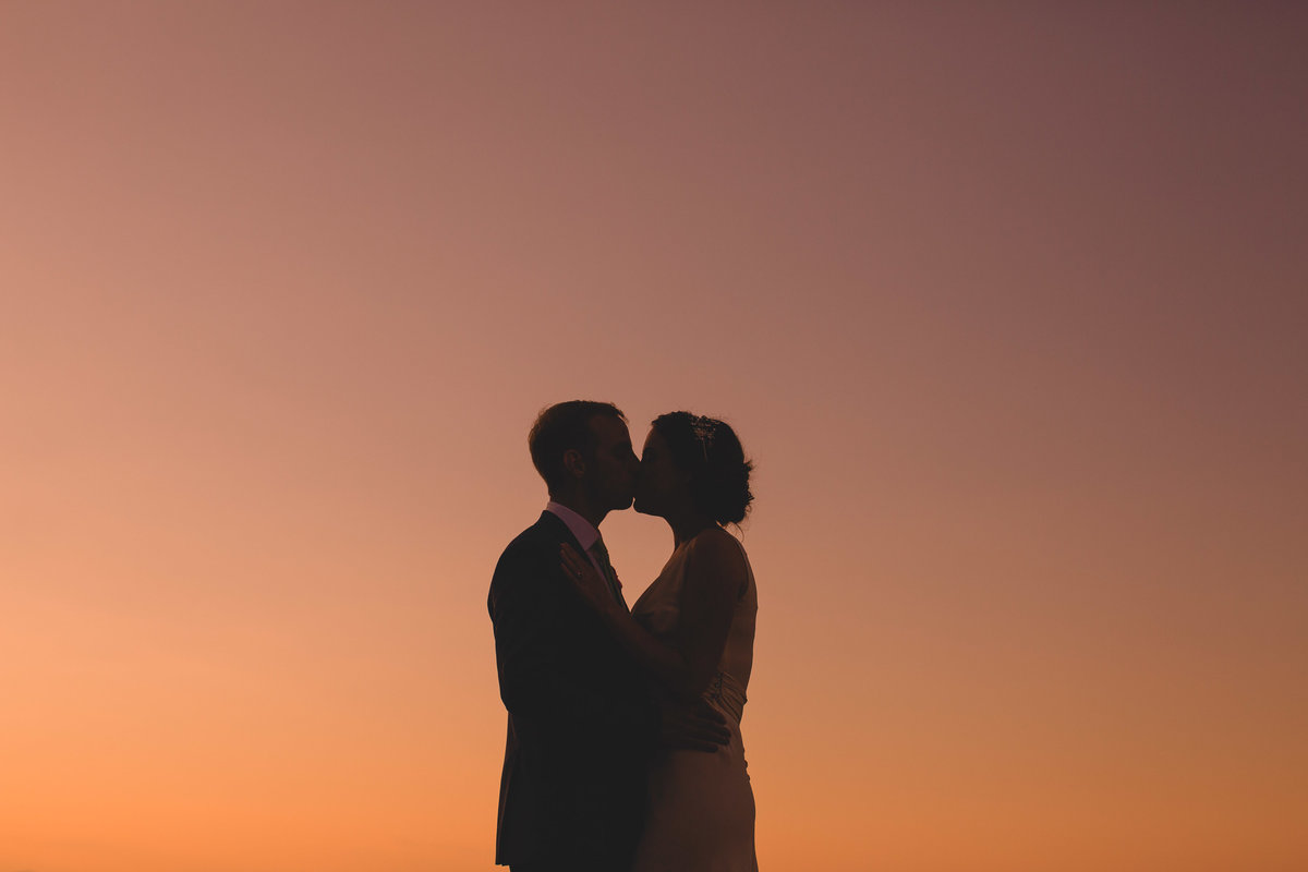 a silhouette sunset photo of a wedding couple