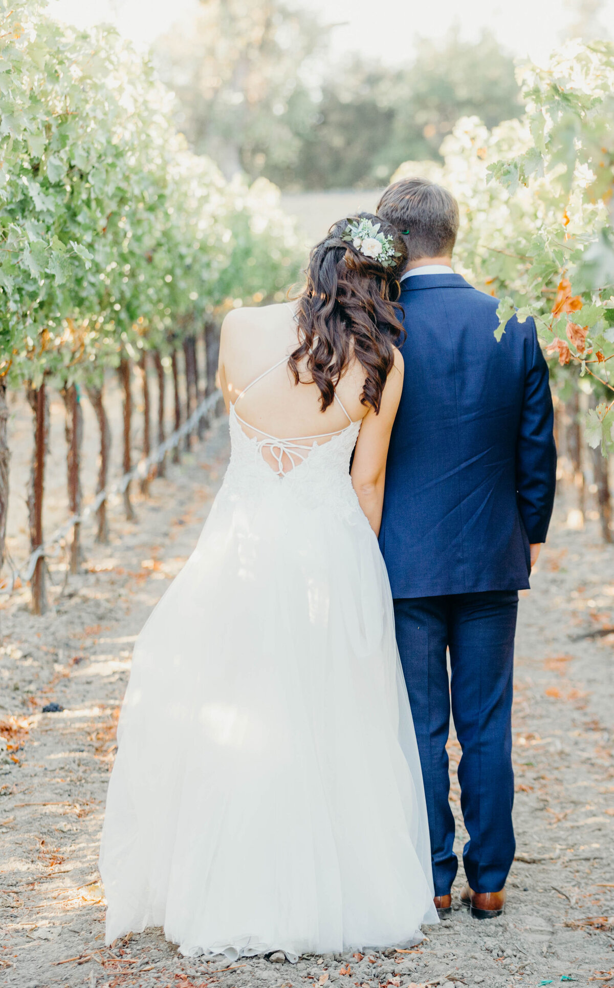 bride and groom standing in the orchard