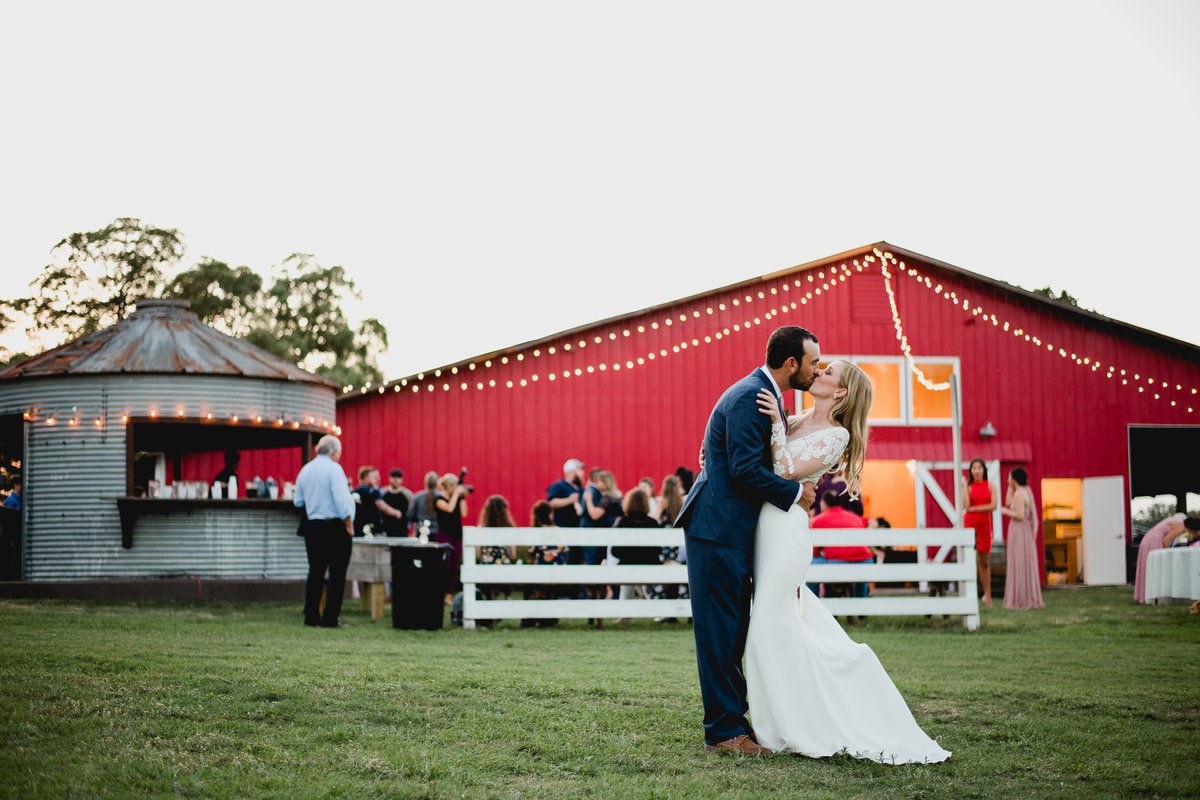 Documentary wedding photographer takes photo of couple in front of their venue with their guests partying in the background. Seven Hills Farm, Trenton Florida.