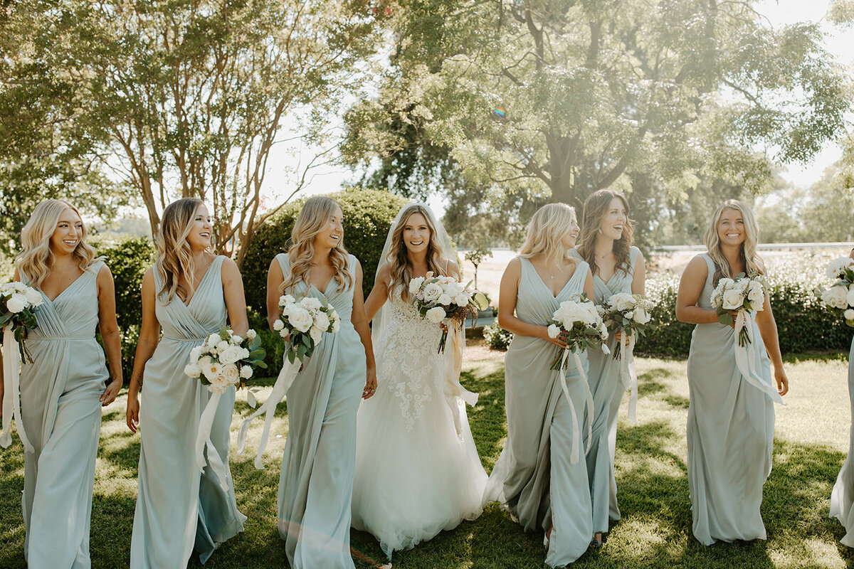 bridal party walking with bouquets