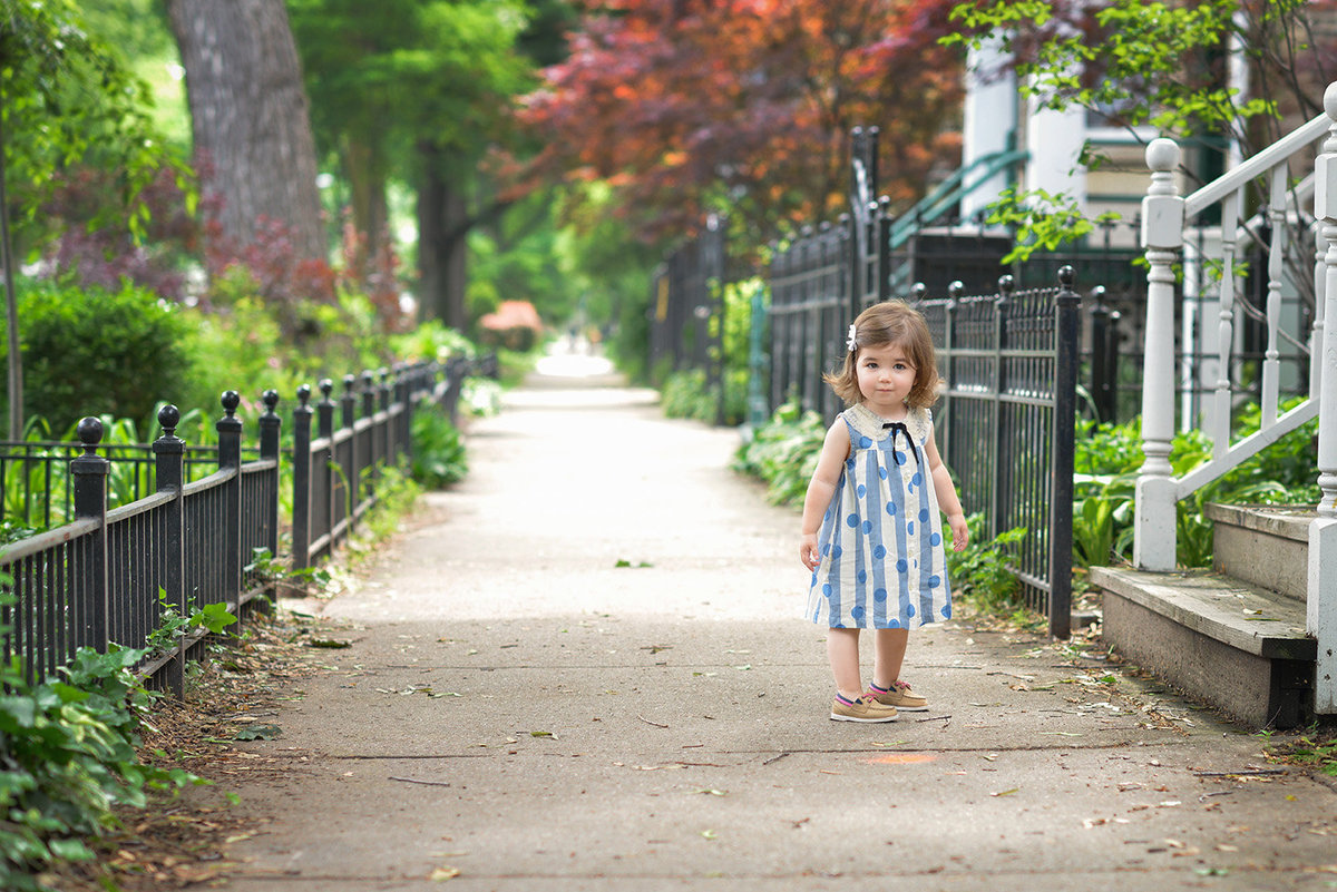 a little toddler girl standing in the sidewalk
