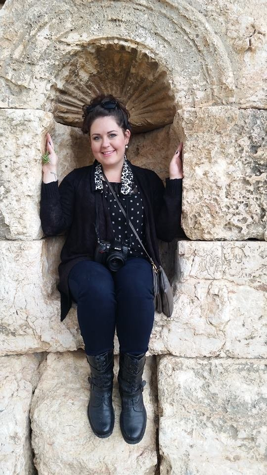 Jill Blue Photography sits in an arch in the Roman ruins of Jaresh, Jordan