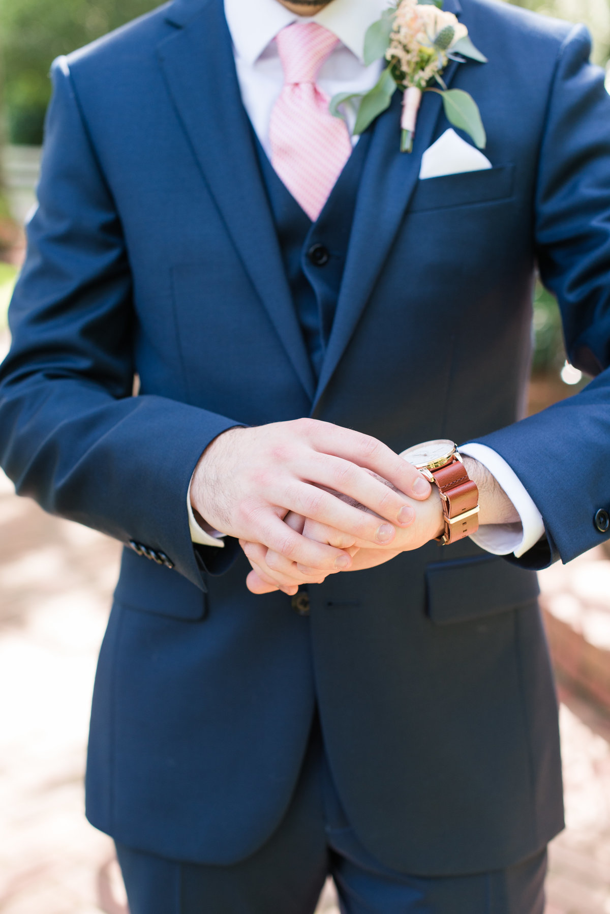 a groom wearing a bright navy blue suit with light pink tie  fixing his watch at Gardens at Gray Gables