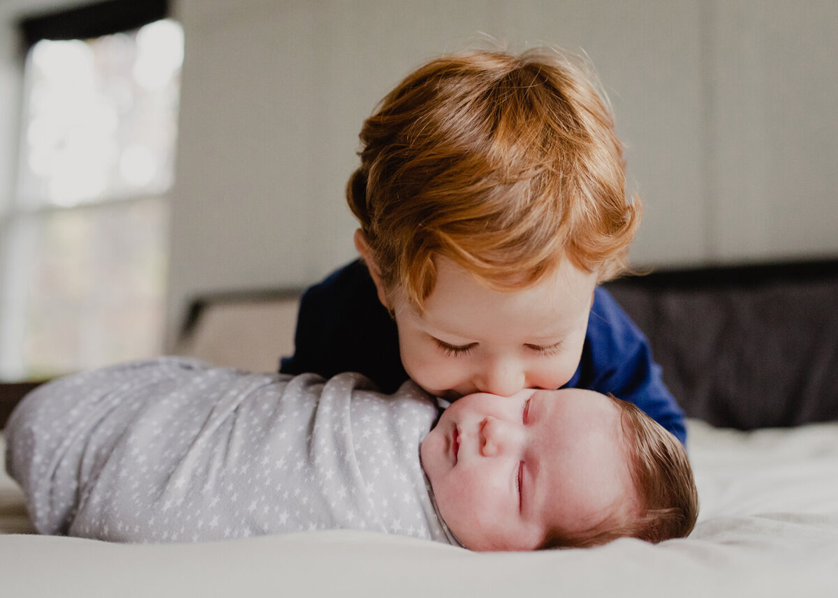 A toddler brother is so excited to meet his new baby brother! He leans over on the bed and kisses his brother while the newborn is swaddled and sleeping.