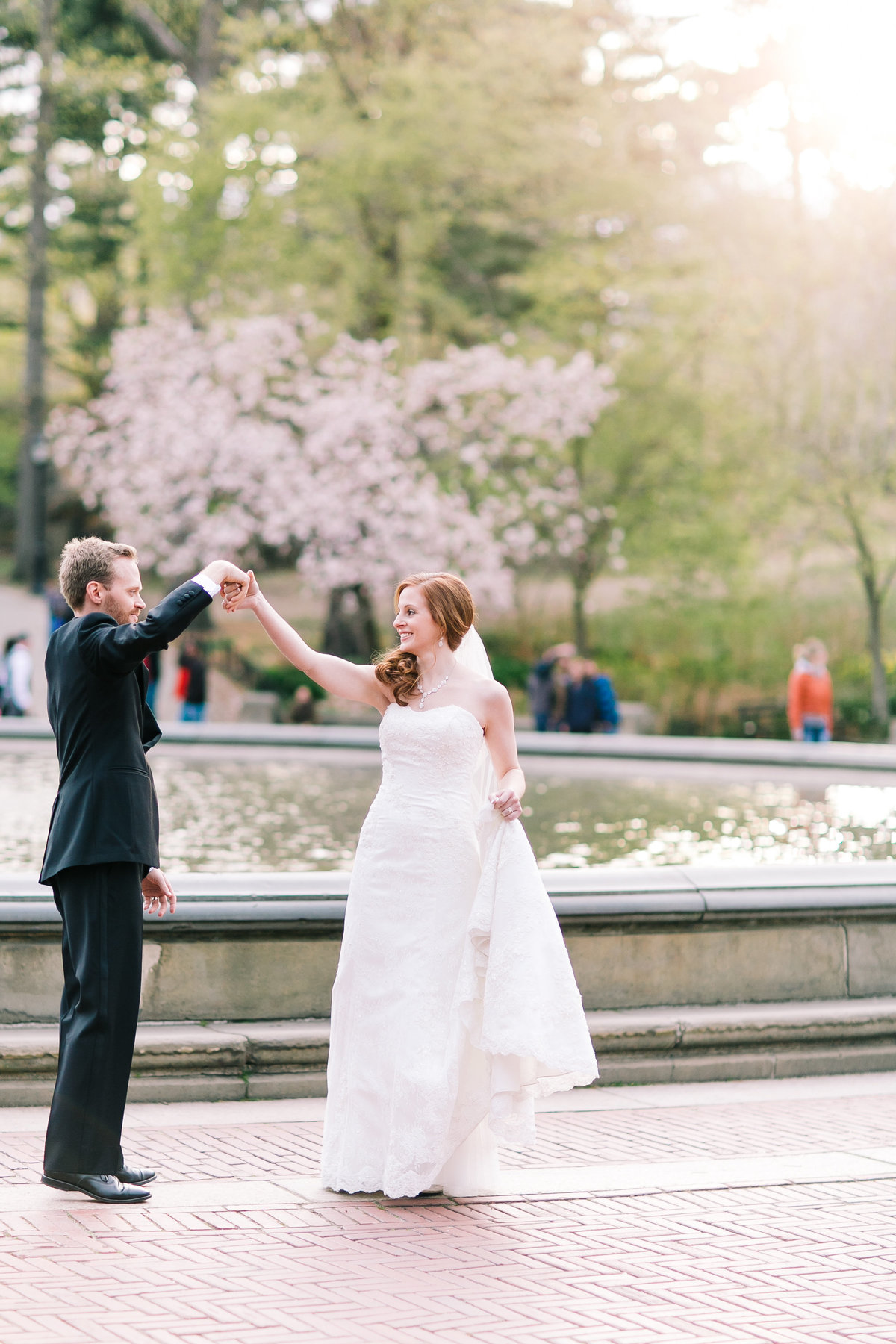 Groom twirling his bride at sunset in central park