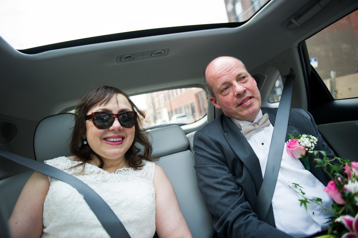 Bride and groom ride to reception venue, back seat, Chicago.