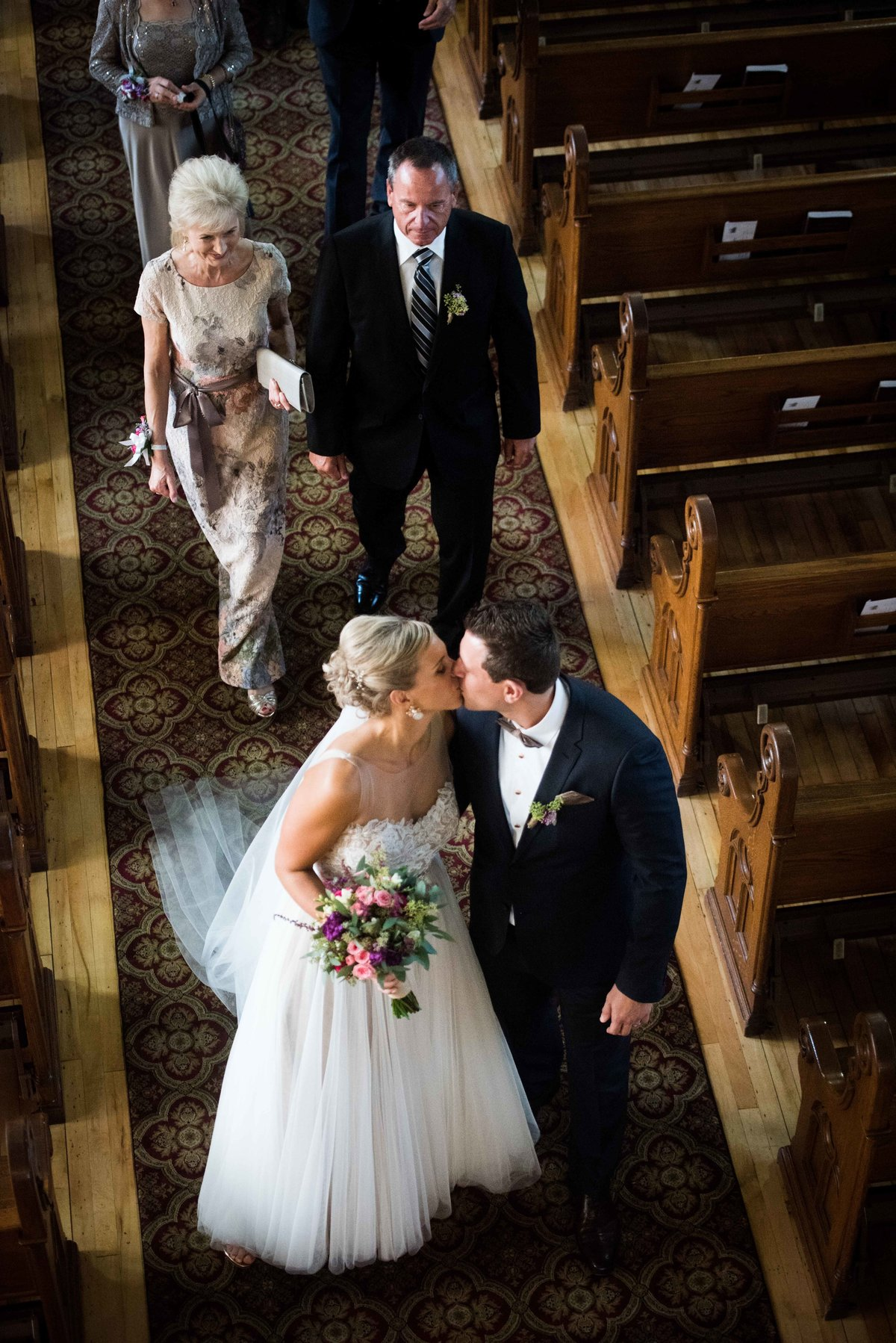 Bride and groom kiss in church aisle, Chicago IL.