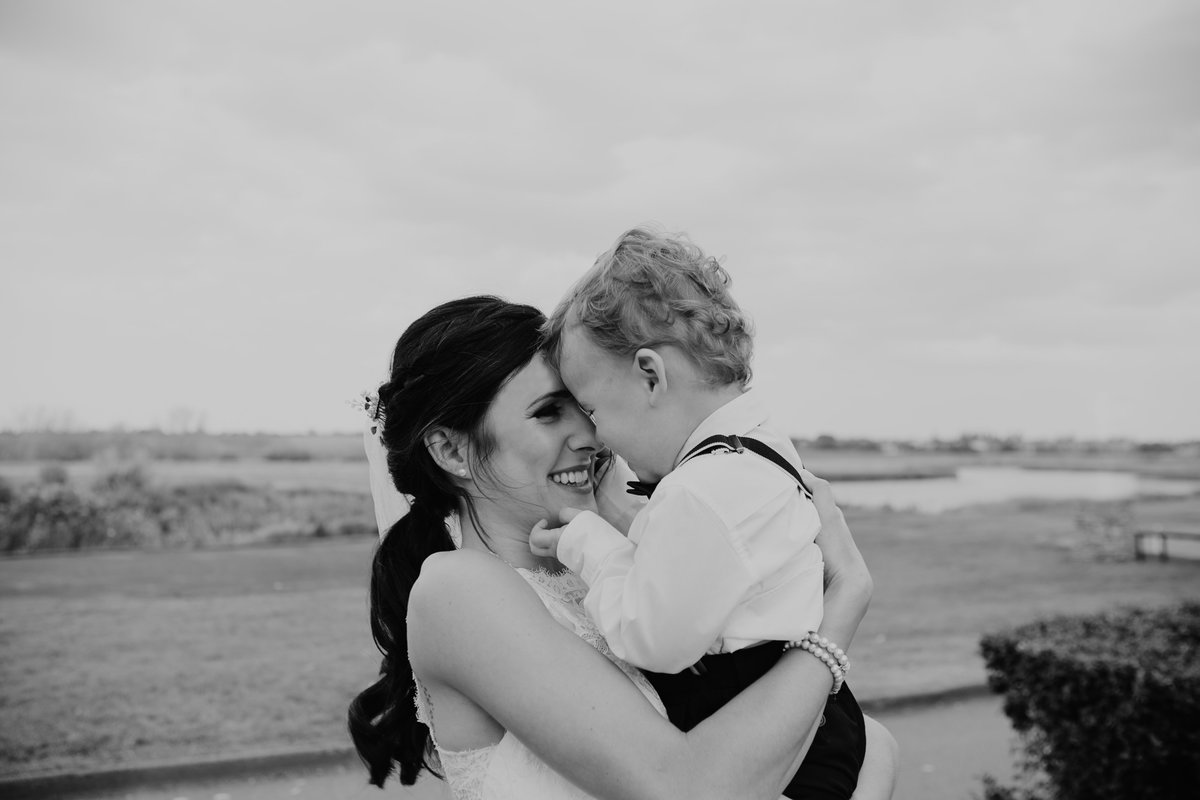 Bride holding her son after wedding ceremony | Regina Wedding Photographer
