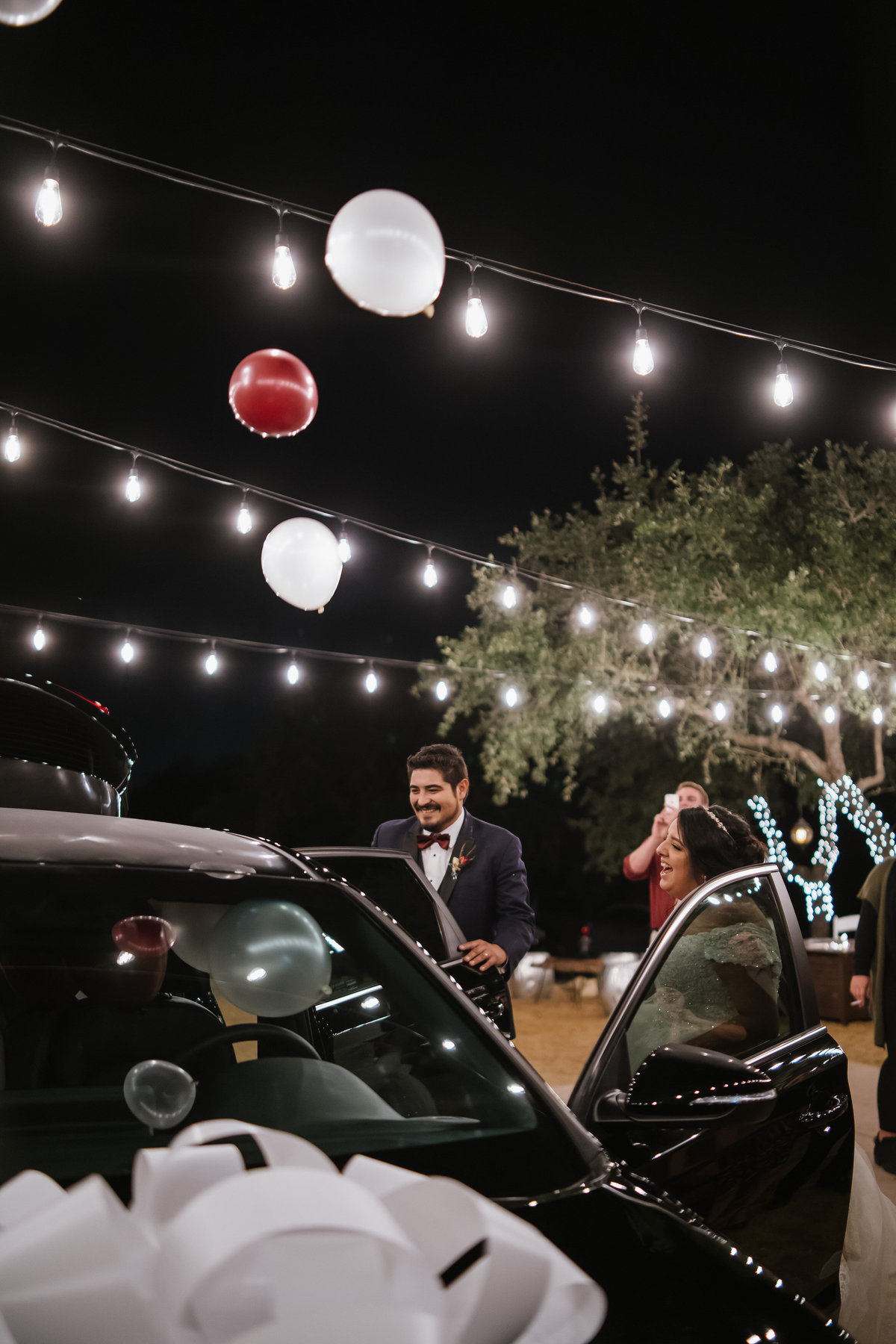 bride and groom open surprise car wedding gift at reception at Oaks at Heavenly Wedding venue in Helotes