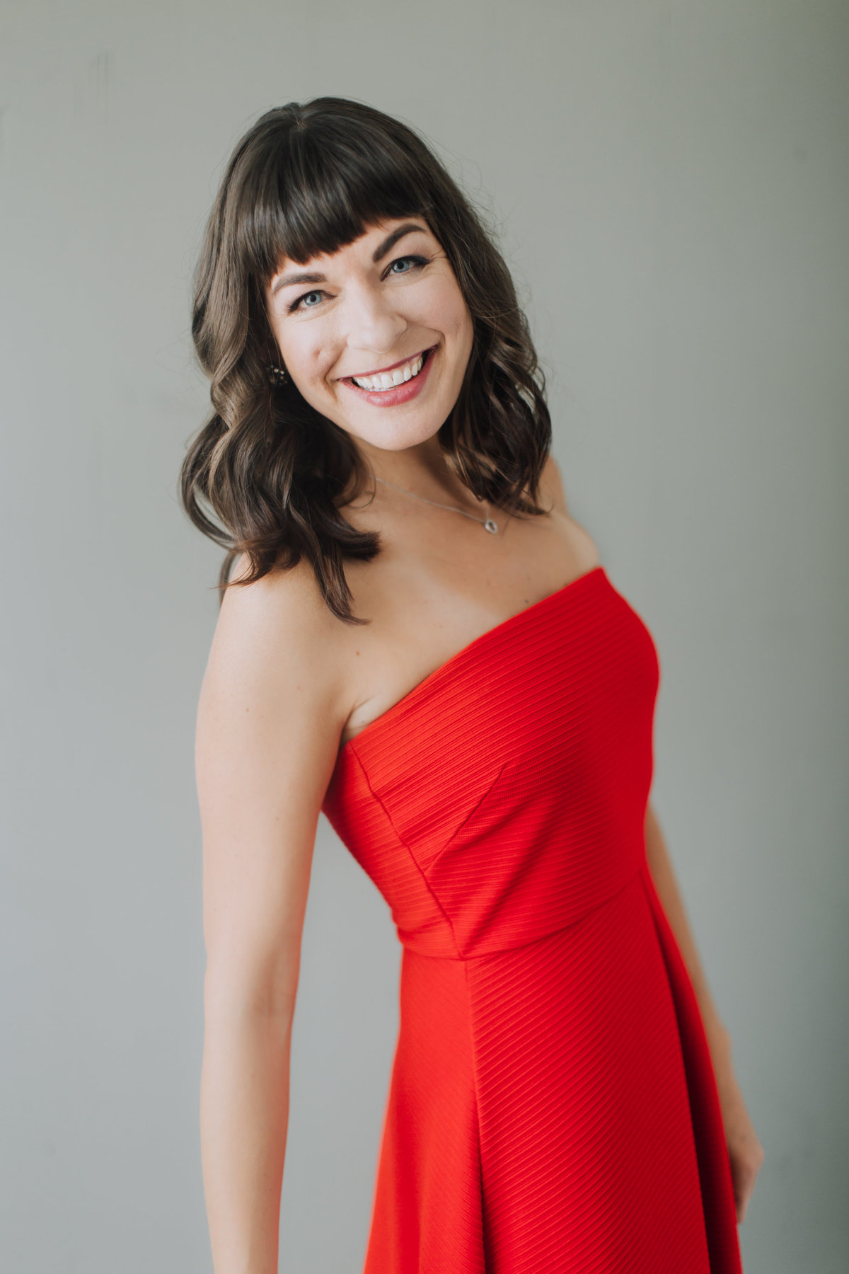 smiling woman red dress studio grey