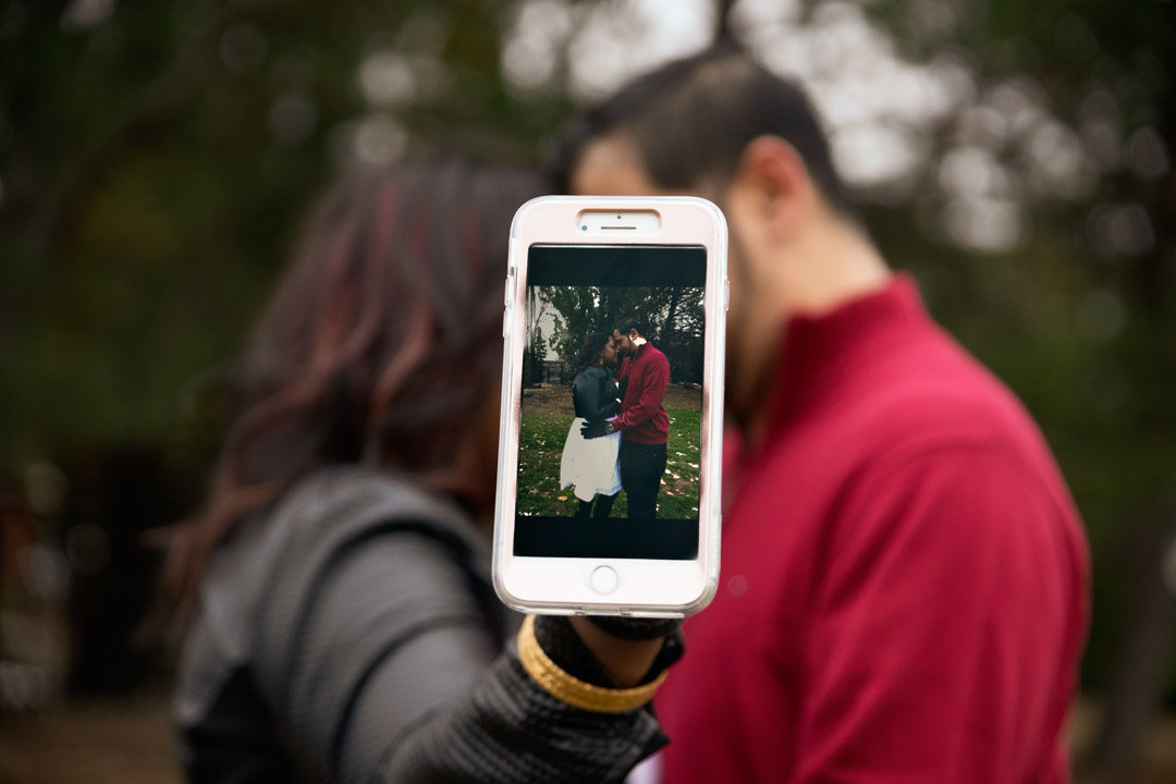 Couple holds cell phone out for a picture within a picture photo while they sneak a kiss