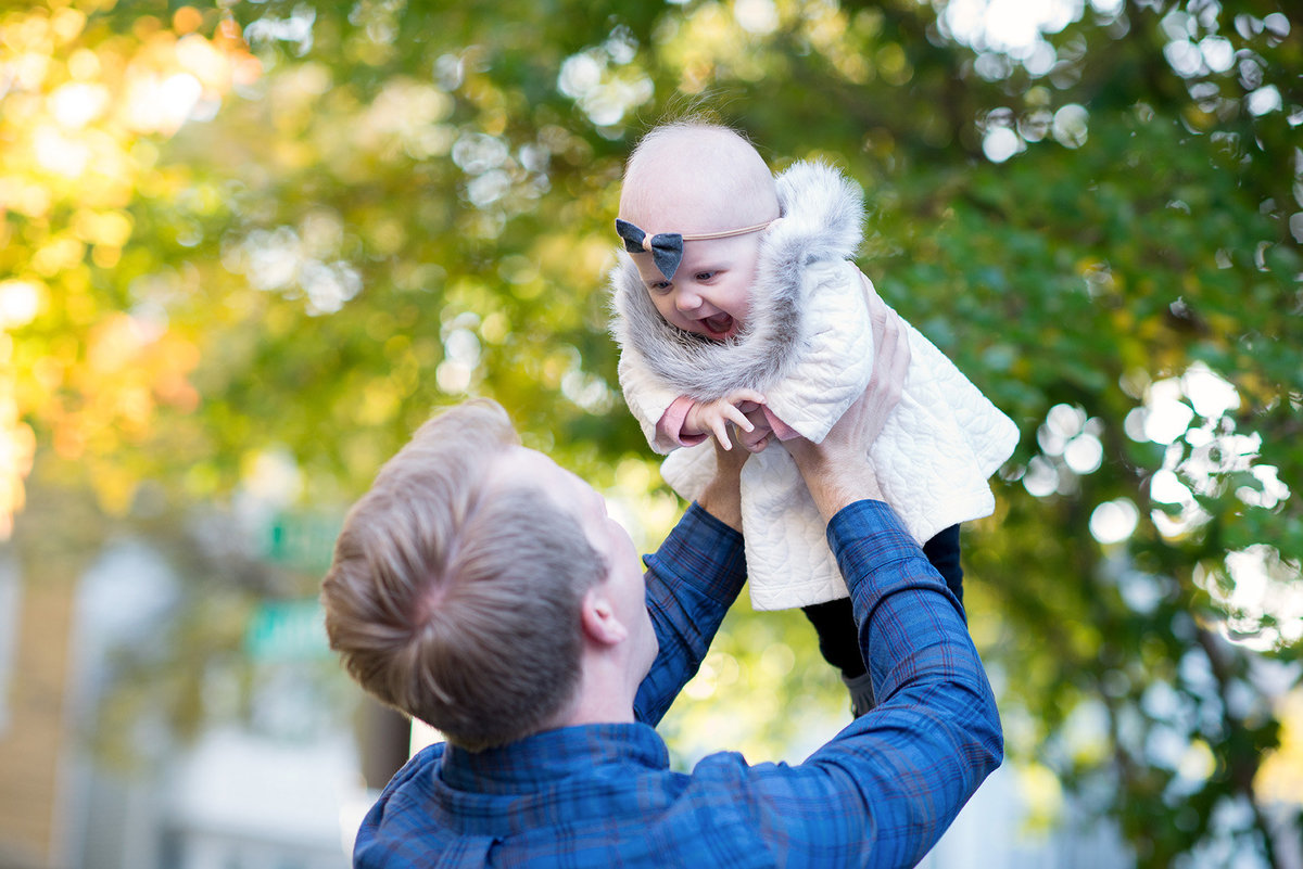 a dad throws his baby girl in the air during golden hour