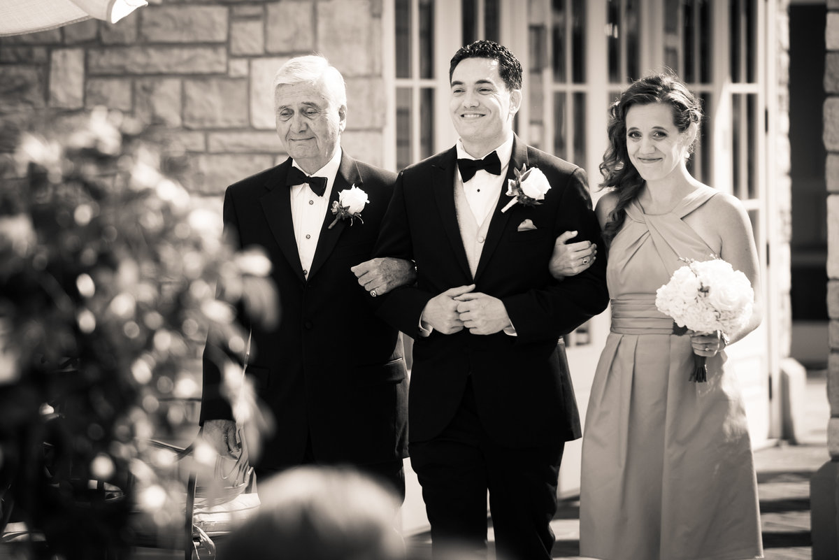 Father and sister escort groom down aisle, Chicago wedding.