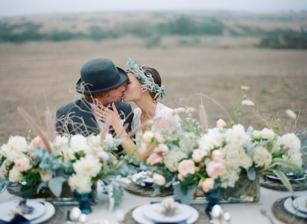 bride and groom sitting at a long head table with flowers