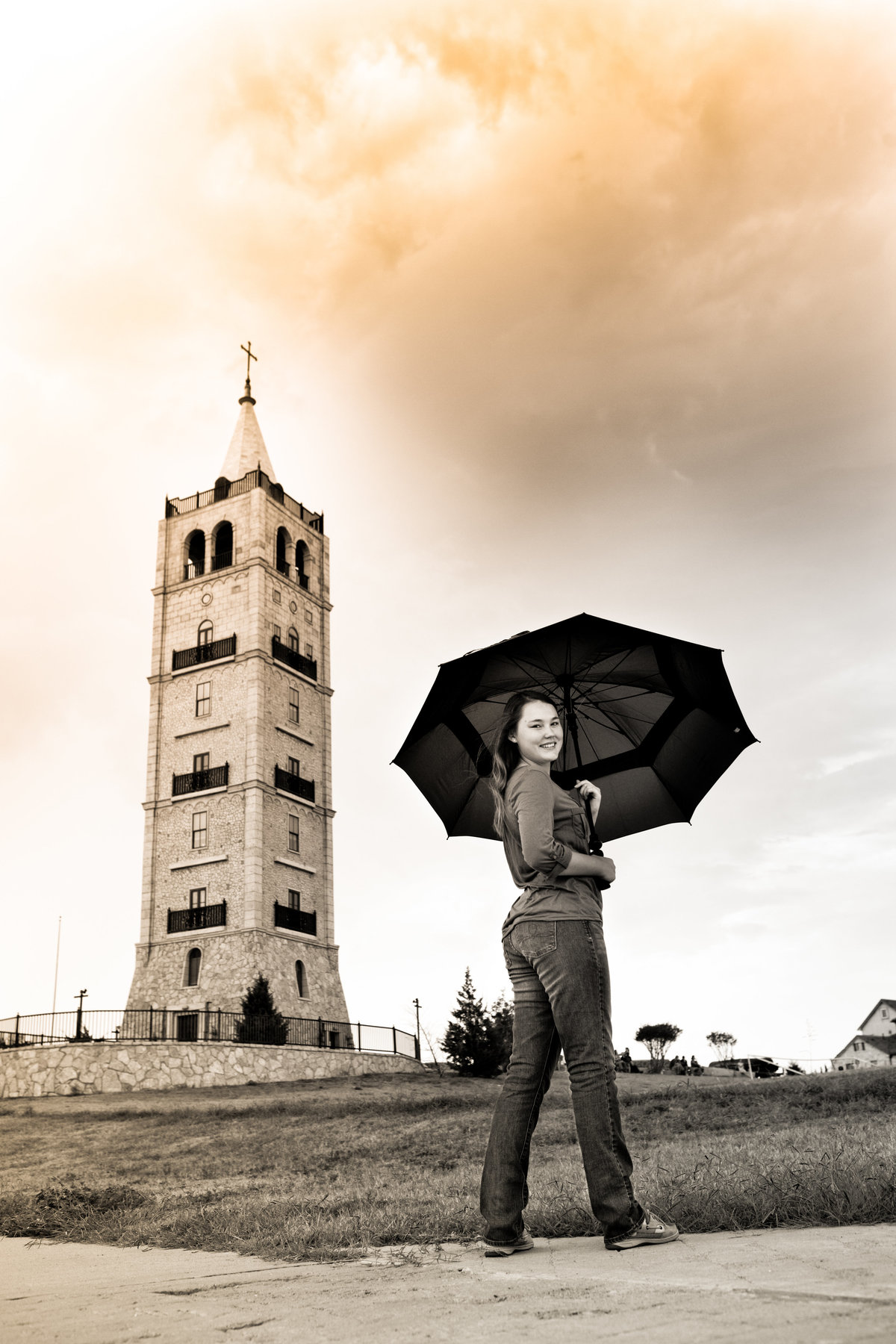 High school senior girl picture with umbrella standing with umbrella in front of tower at Adriatica Village McKinney Texas with ominous clouds