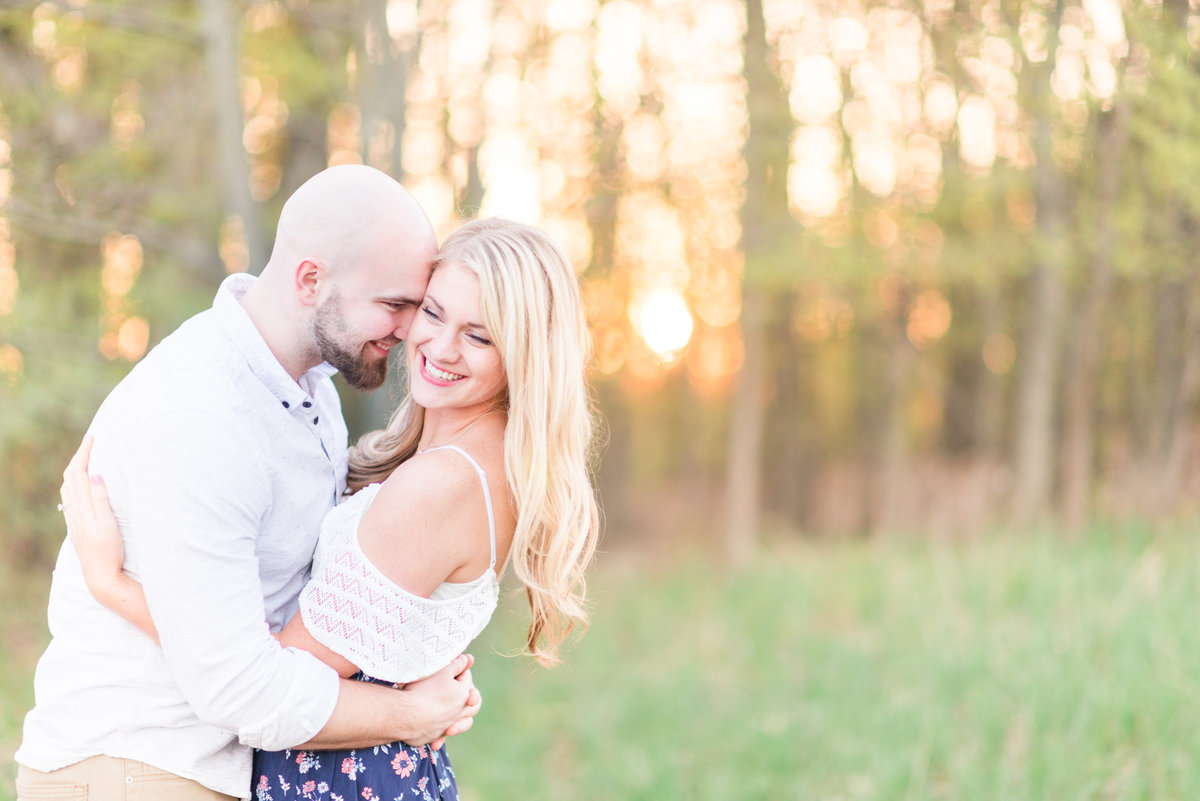 spring engagement portraits in the blooming cherry blossom orchard of michigan
