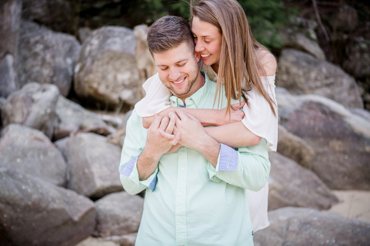 She hugs him from behind and smiles against his ear at Cumberland Falls State Resort engagement photo by Knoxville Wedding Photographer, Amanda May Photos.