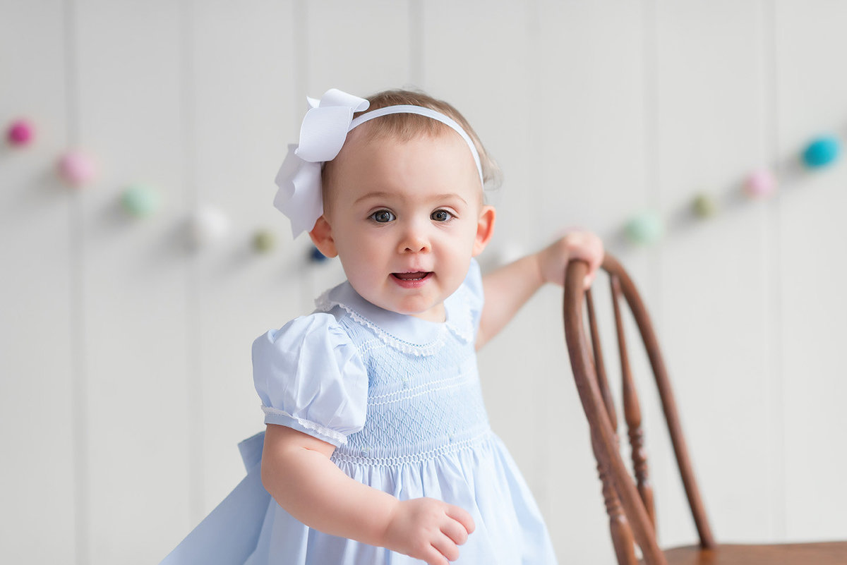 a baby girl stands holding a chair