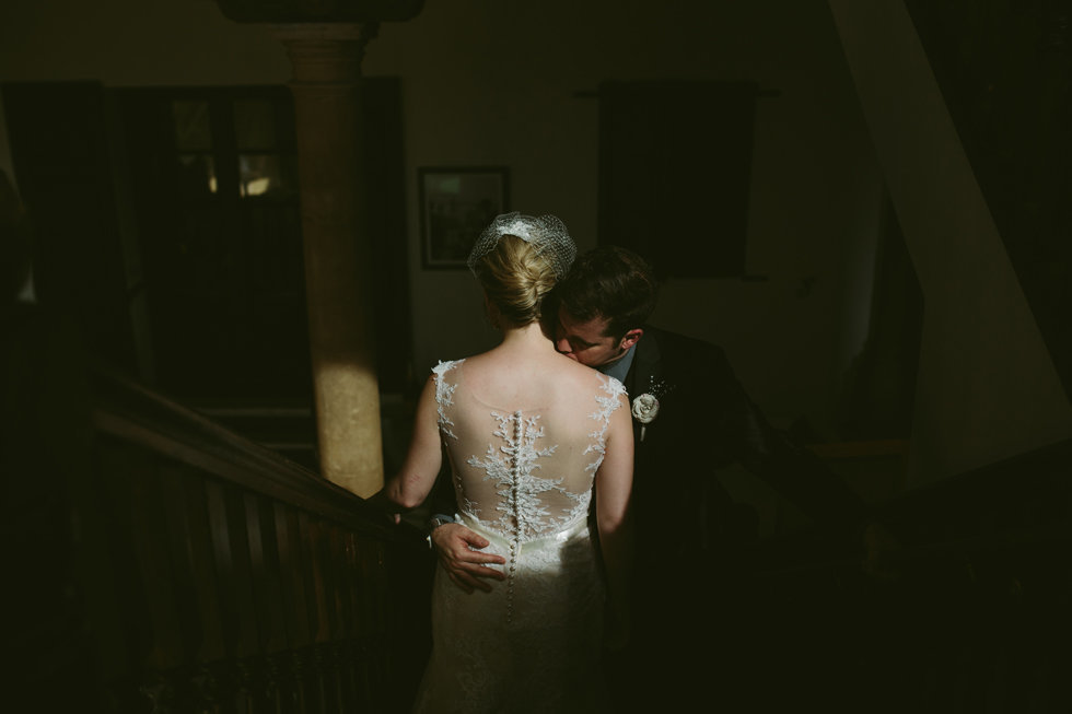 Bride and Groom kiss in a pocket of light, Wrigley Mansion