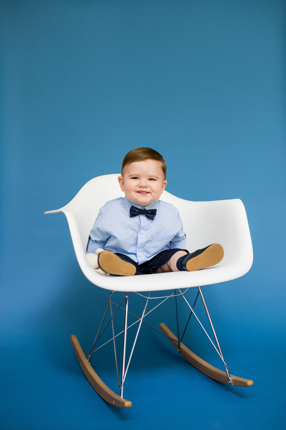 Baby sitting in Eames Molded Plastic Armchair Rocker chair on blue backdrop for baby's first year photography session.