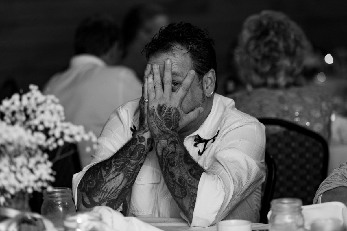 tattooed father of bride peeking through fingers