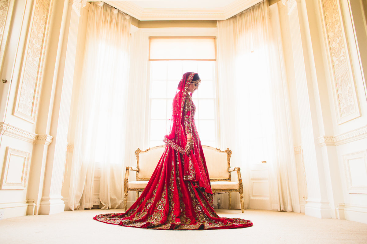 bride wearing a red sari in the window of the bridal suite at hedsor house