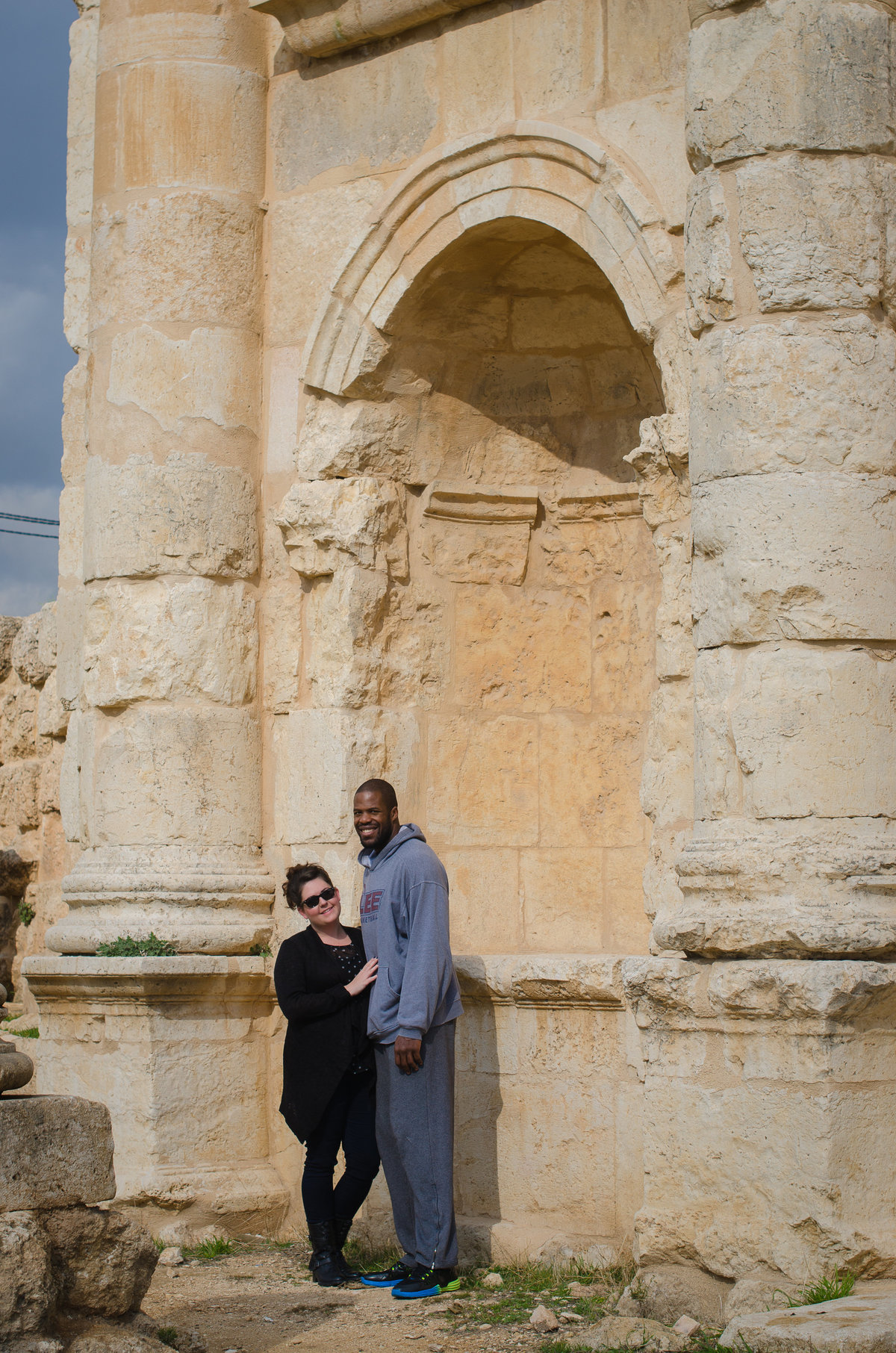 Jill and Desmond Blue standing in an arch at the Roman ruins of Jaresh, Jordan