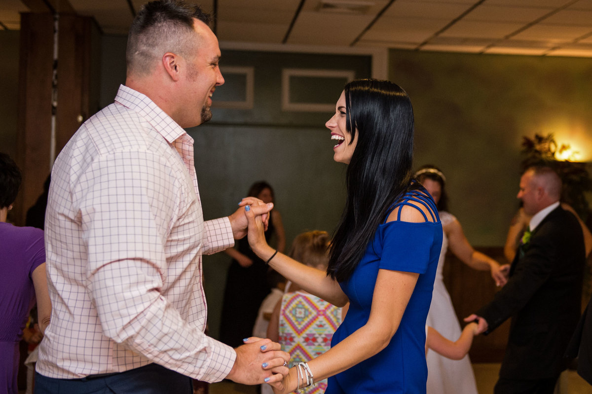 guests on dance floor holding hands laughing