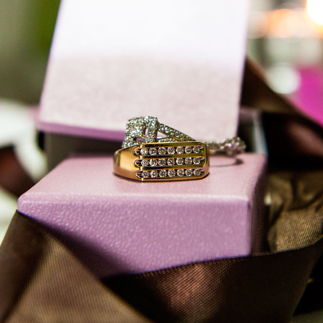 wedding rings for both bride and groom sitting on top of michael hill jewelry purple boxes with brown ribbon