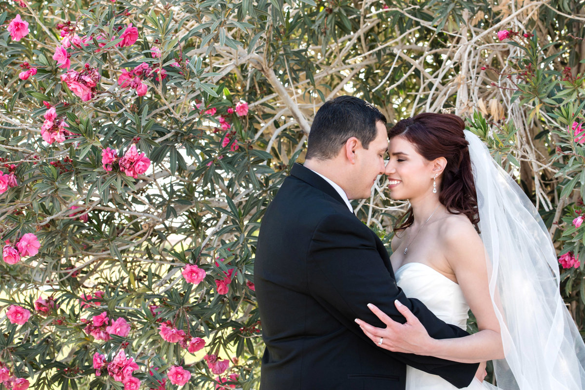 bride and groom in front of bougainvillea