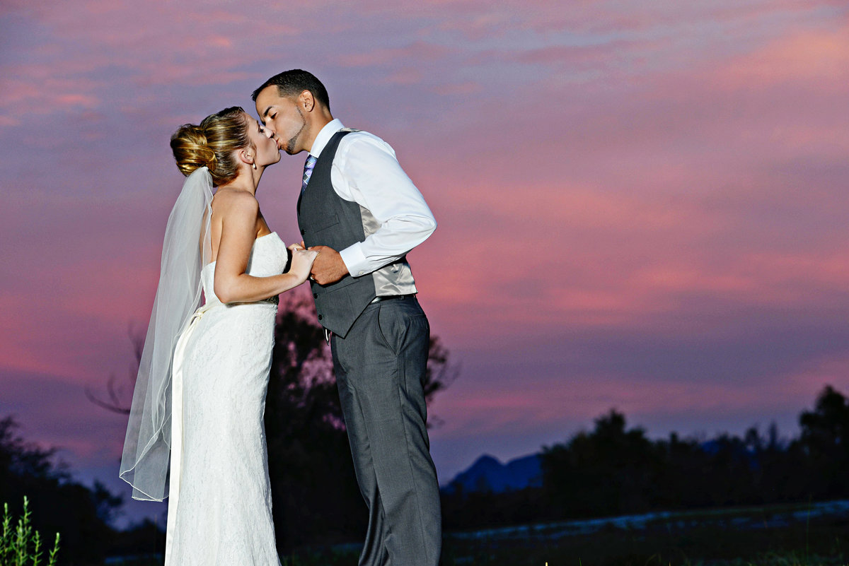 bride and groom kissing in front of sun set in Roll, Arizona