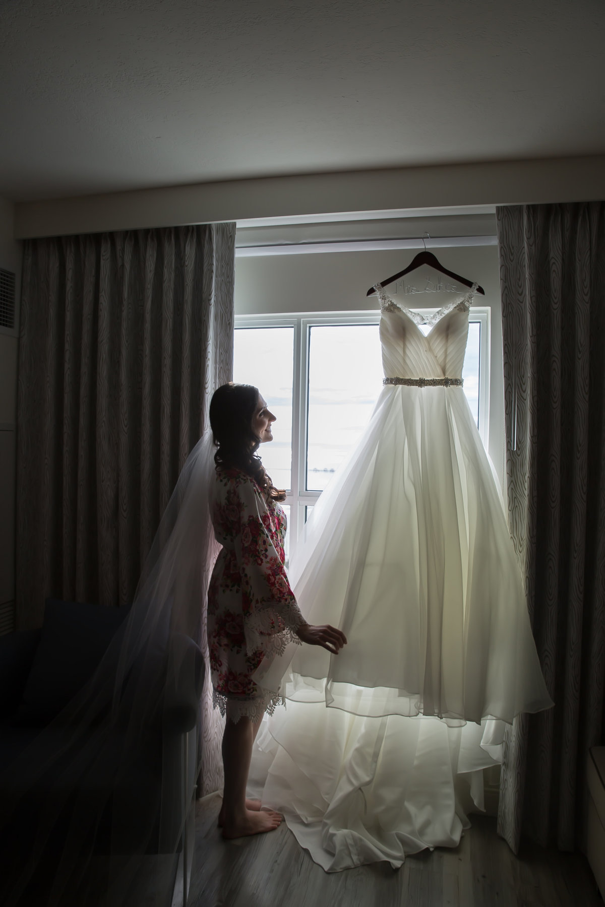 Bride looking at wedding dress in window on wedding day in Gulfport MS