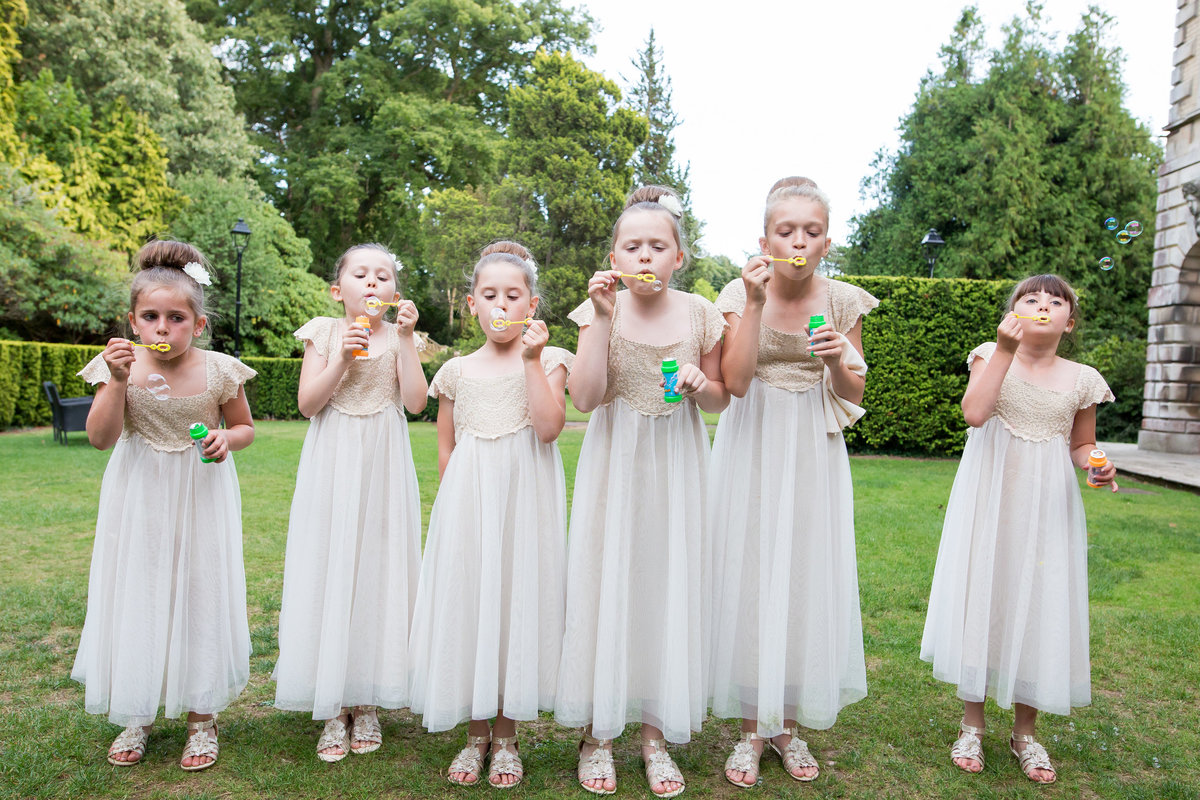 flower girls blowing bubbles at exeter reed hall wedding