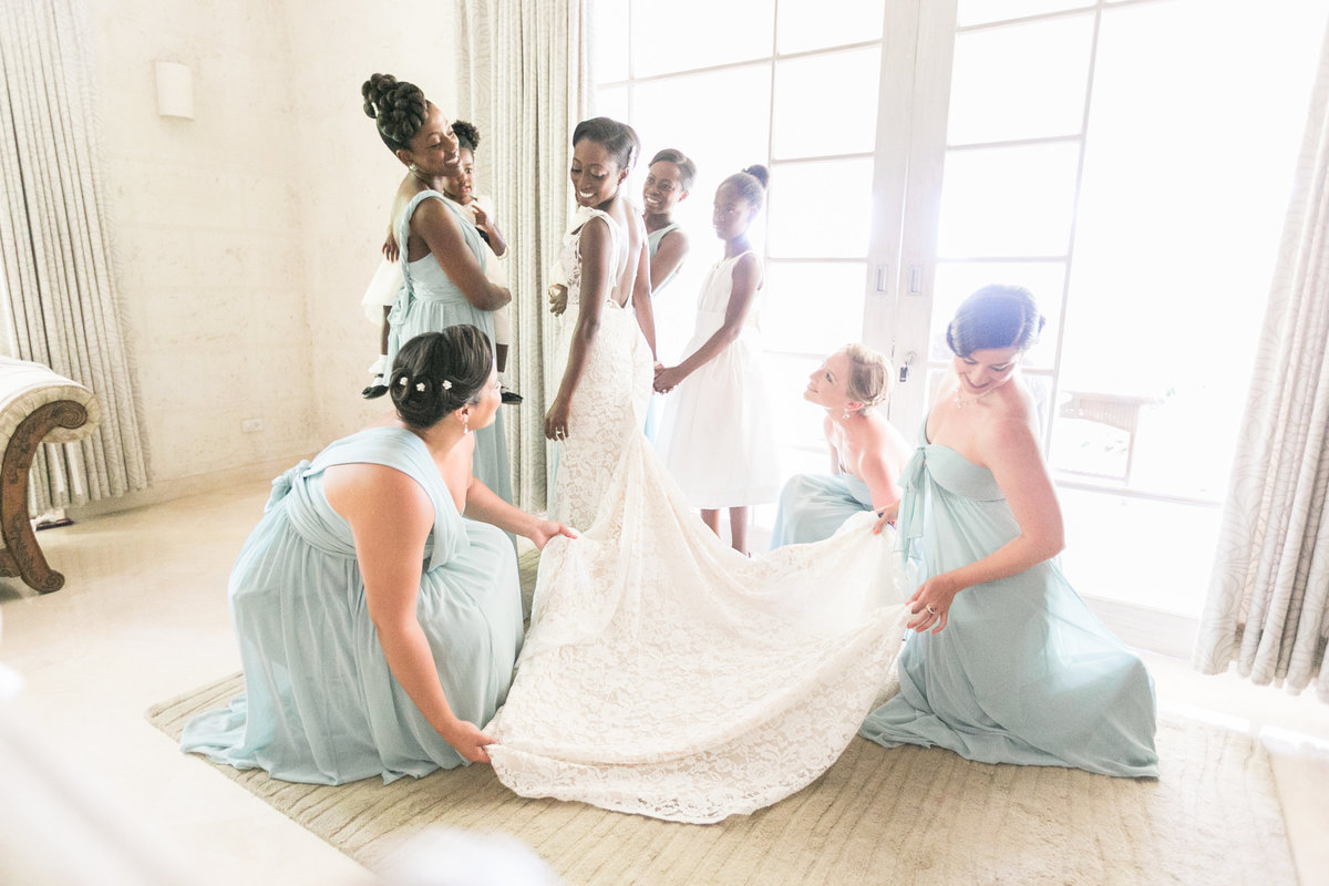 Bridesmaids helping bride with wedding gown in candid moment