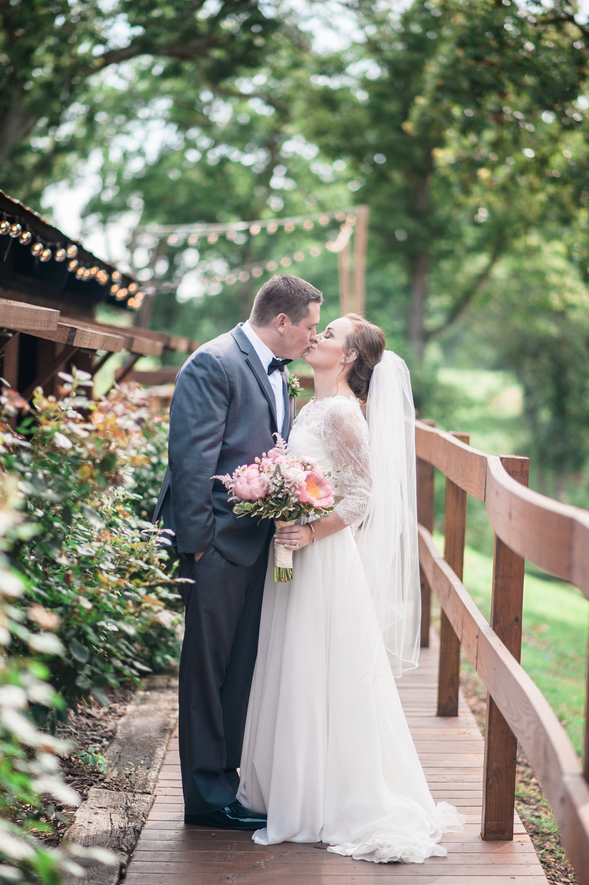 Barn at The Spring rustic Fayetteville wedding  Bride and Groom  kissing in a vineyard taken by Northwest Arkansas Wedding Photographer Christy Simply Bliss Photography