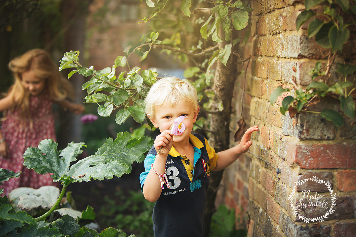 little boy in garden holding flower