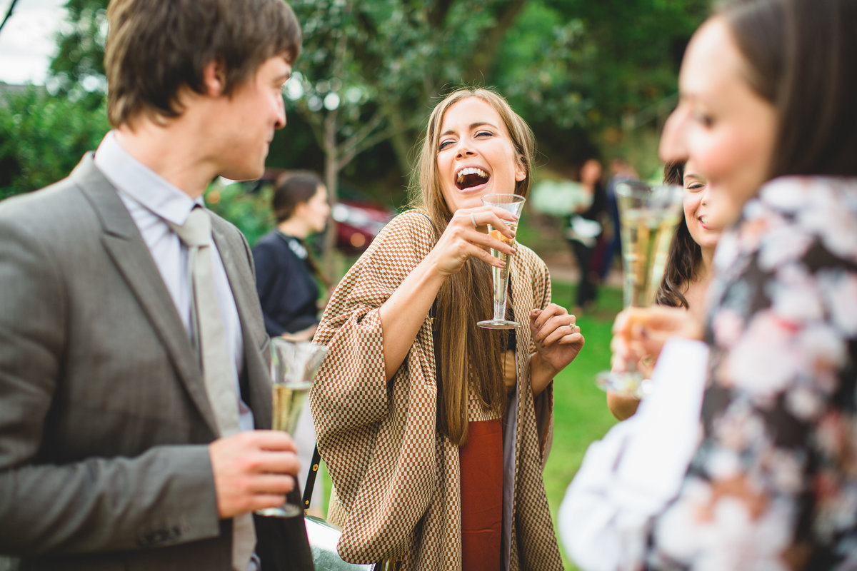 girl laughing at drinks reception drinking champagne