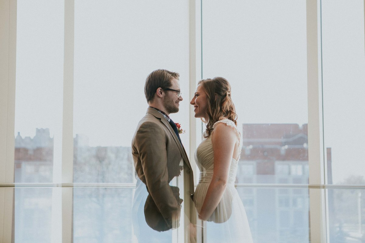 Couple stands in front of window at Ball State wedding