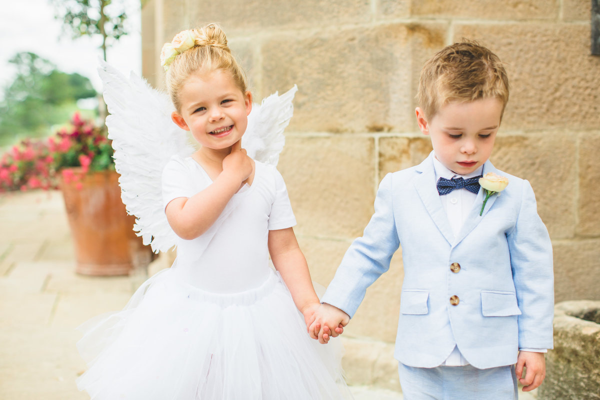 a flower girl with angel wings and a page boy in a blue suit with dicky bow before the wedding ceremony